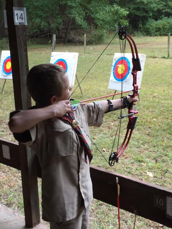 Scout holding a bow and aiming at target