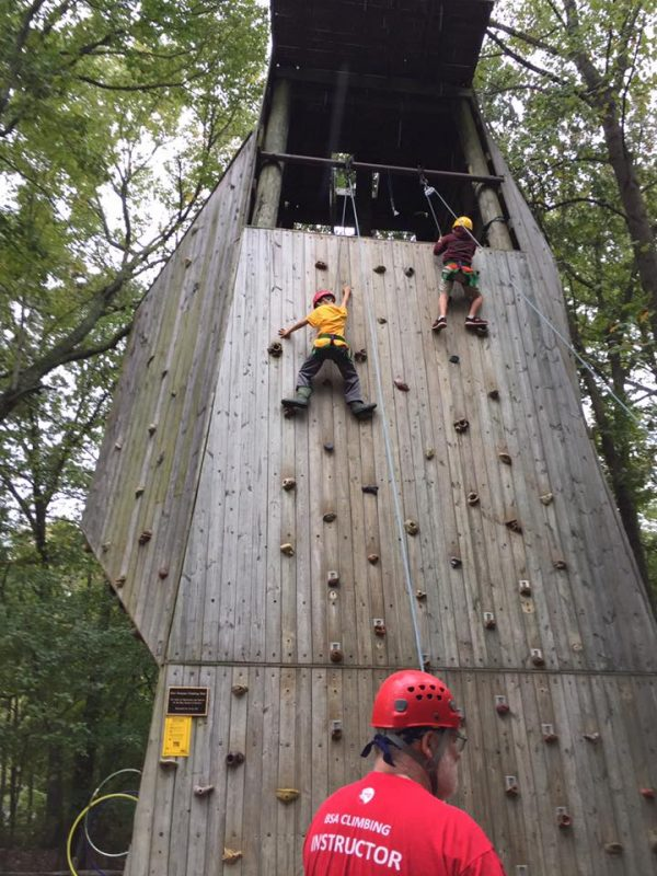 Kids going up a wood and rock climbing wall