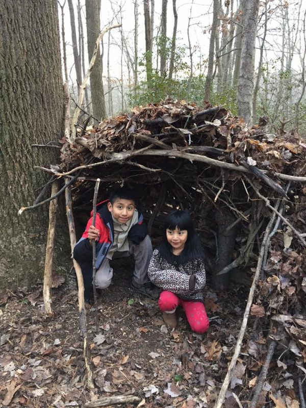 Scouts outside under a stick and leaves hutch they constructed