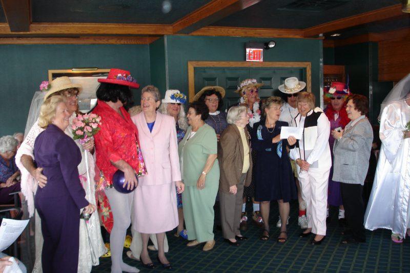 People standing inside, many wearing fancy easter hats