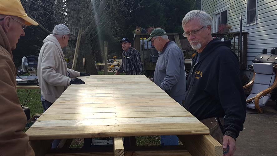 Men working on a wood wheelchair ramp