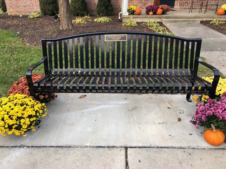 Metal bench with fall flowers sitting around it