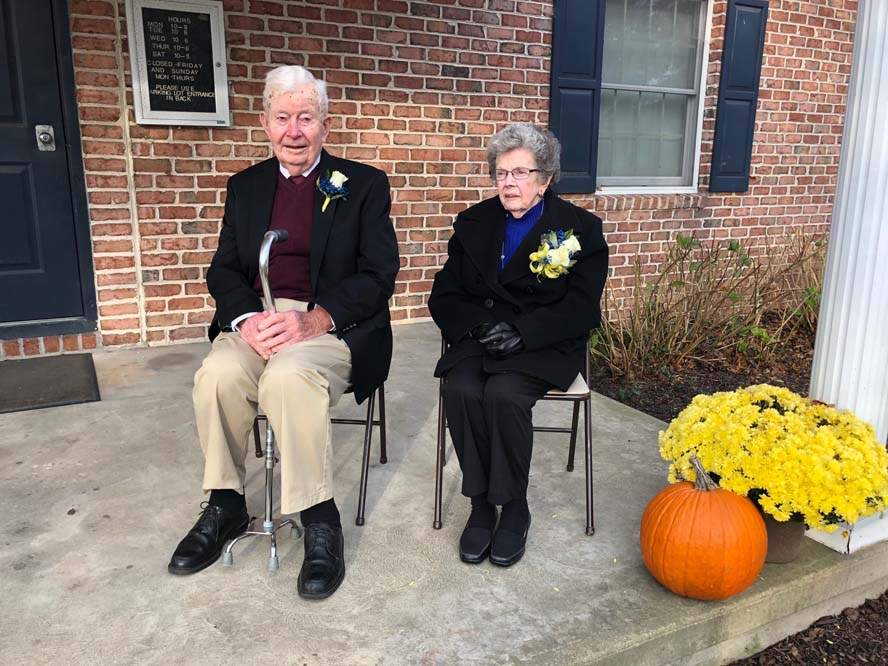 Older man and woman sitting on chairs on porch