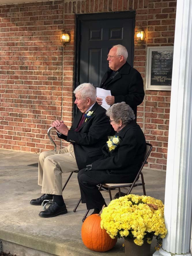 Senior citizens sitting on porch with flowers and pumpkin decorations