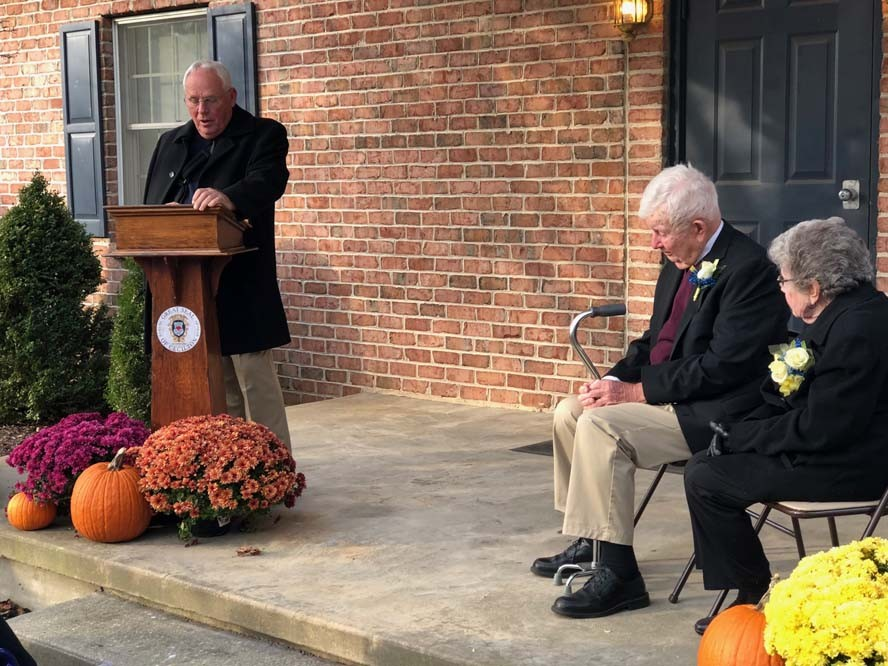 Man speaking behind podium with two senior citizens sitting nearby
