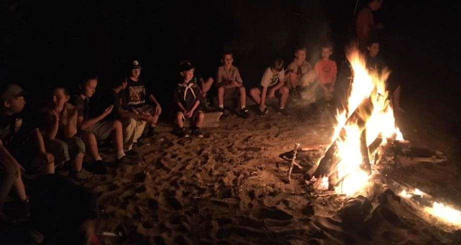 Scouts sitting around burning campfire at night