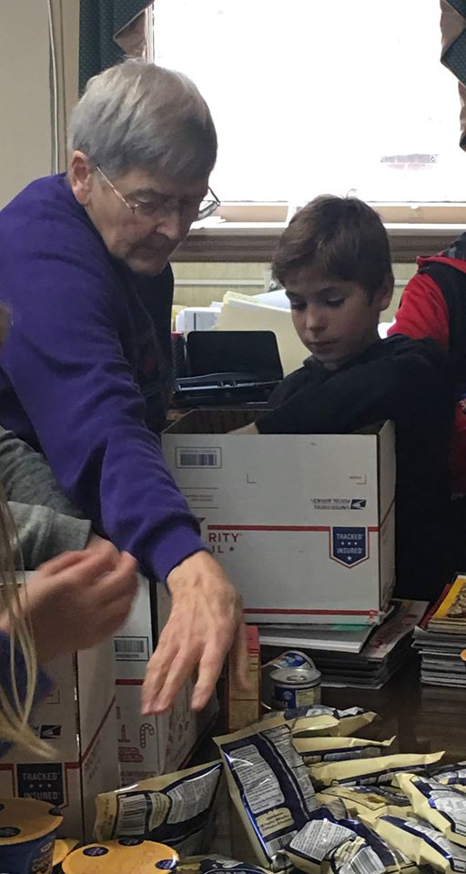 Older woman and young boy packing care box