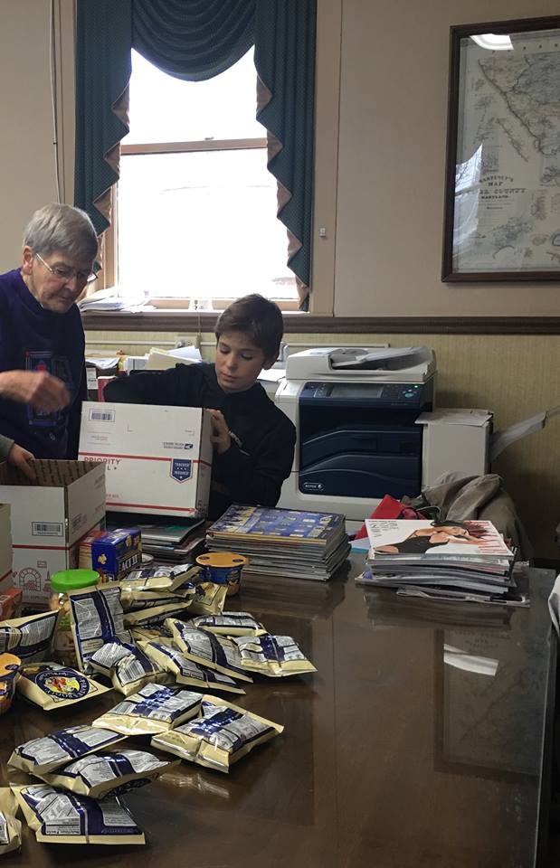 Boy packing care package using priority mail box