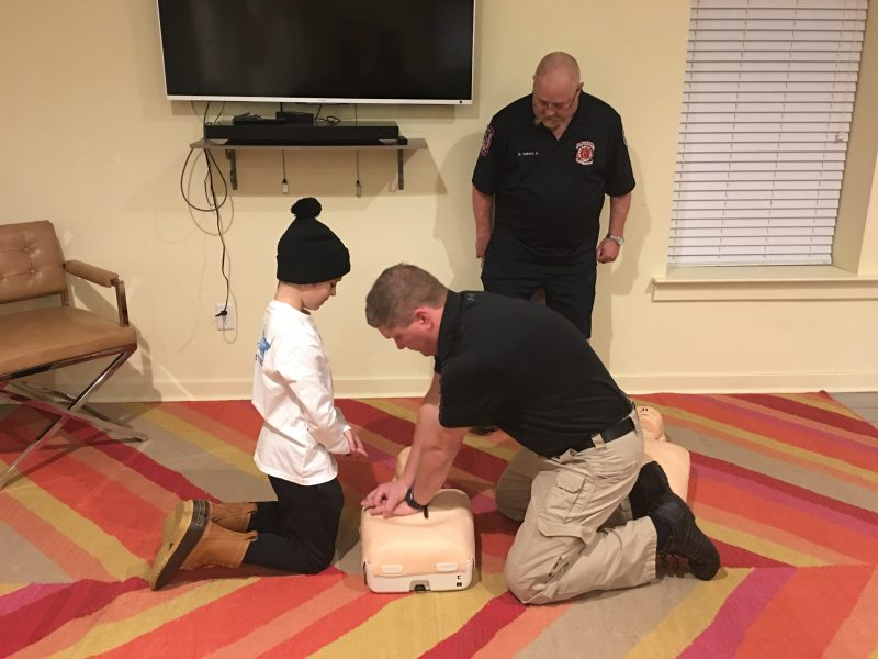 First responder demonstrates chest compressions using a dummy