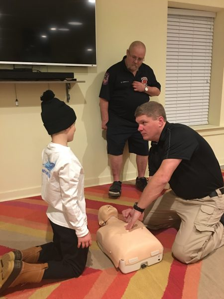 Young boy being shown CPR by a first responder using a dummy