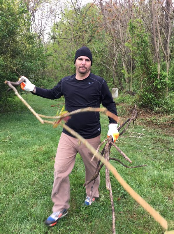 Man carrying tree branches during cleanup