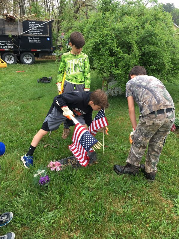 Boys placing American flags in cemetery