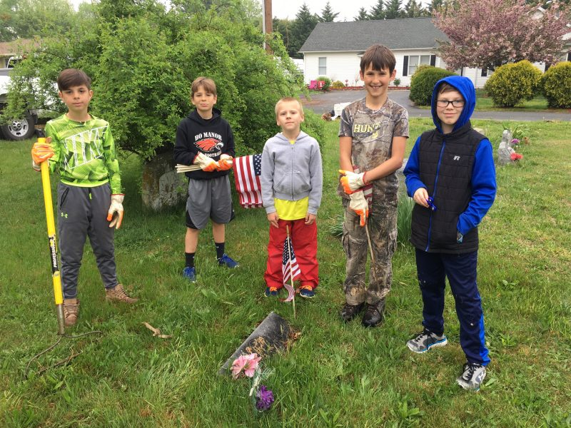 Group of 5 boys pose during cemetery cleanup