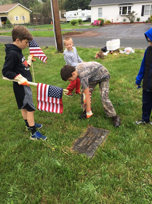 Three boys placing American flags on cemetery grave marker
