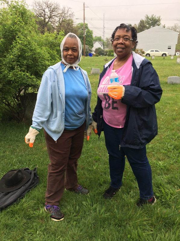 Two ladies pose for camera during a town cleanup