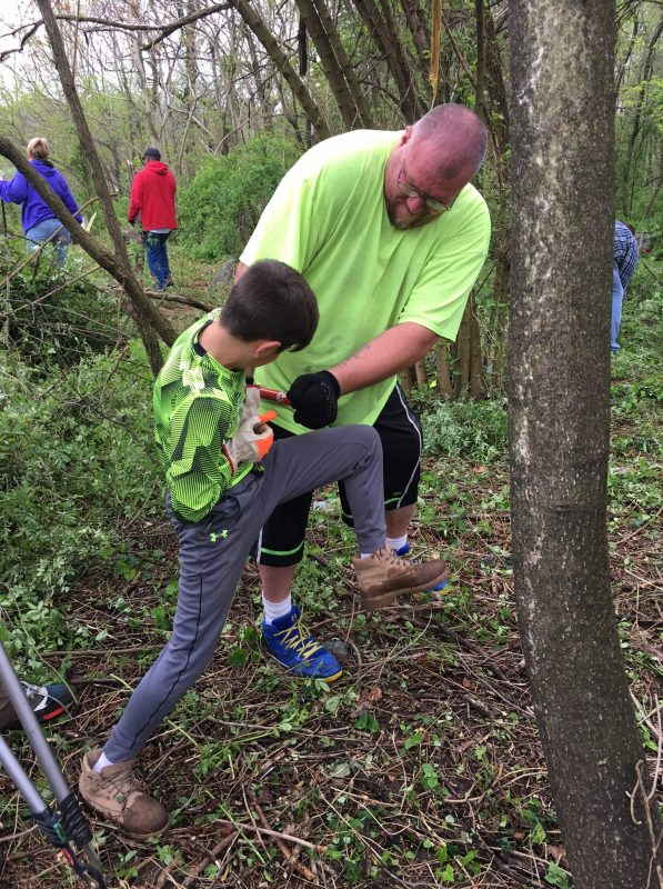 Adult man helps a boy cut a small tree