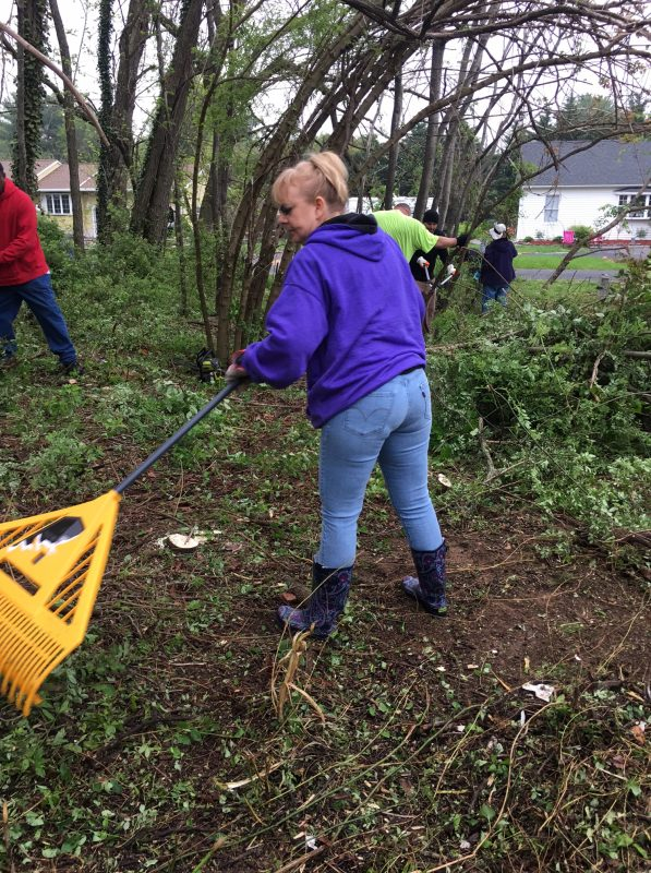 Woman raking up leaves and debris during cleanup