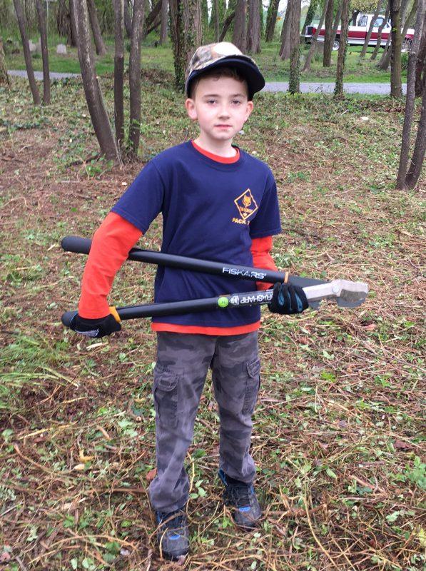 Boy holding a limb cutting tool