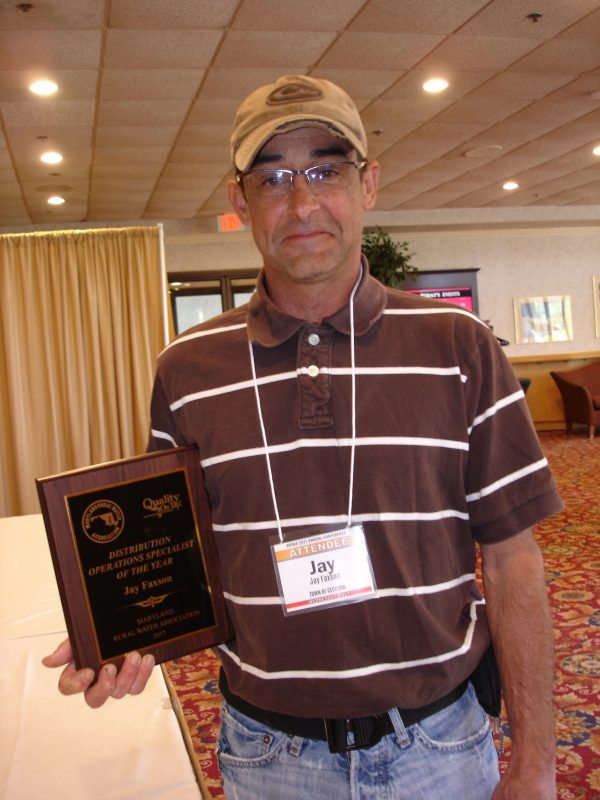 Man with nametag saying Jay holds plaque