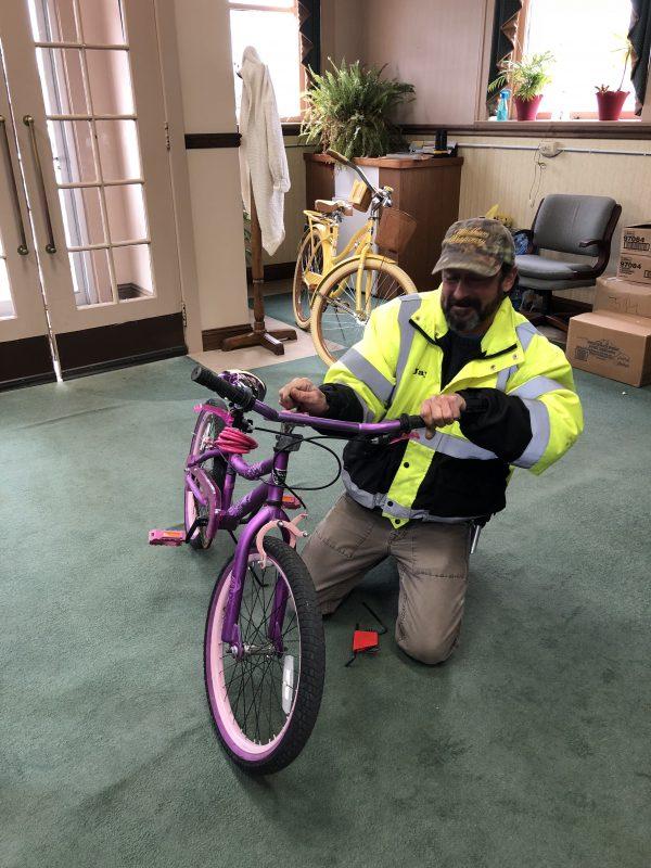 Man in reflective jacket kneeling next to bike