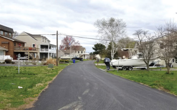 Paved road with houses on either side