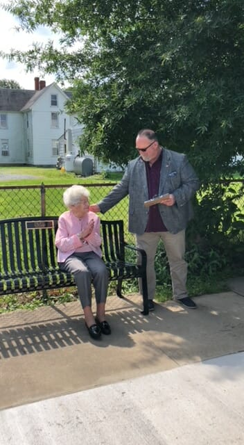 Mayor speaking with Miss Becky as she sits on her bench