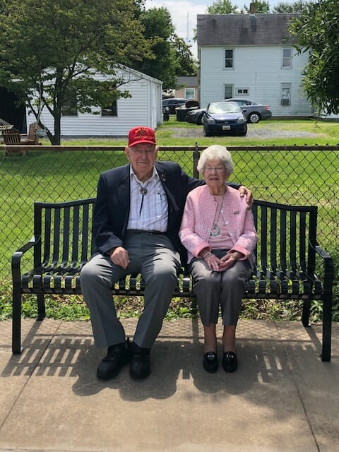 Miss Becky sits on bench with a man wearing red cap