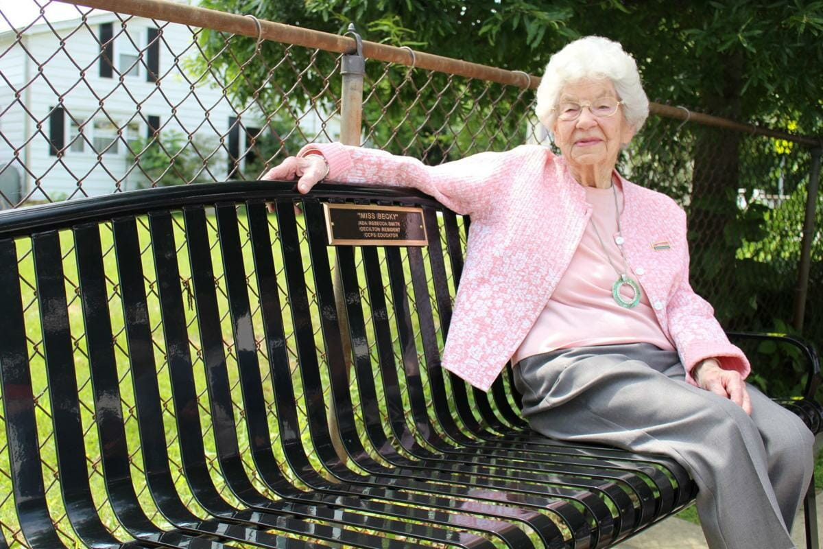 Rebecca Smith sit on the metal bench dedicated to her