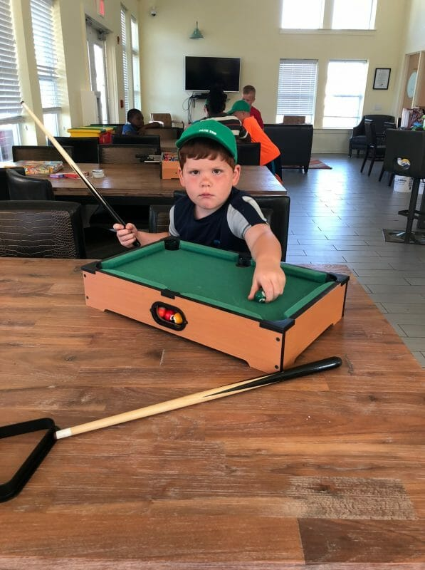 Serious looking boy playing with the mini pool table
