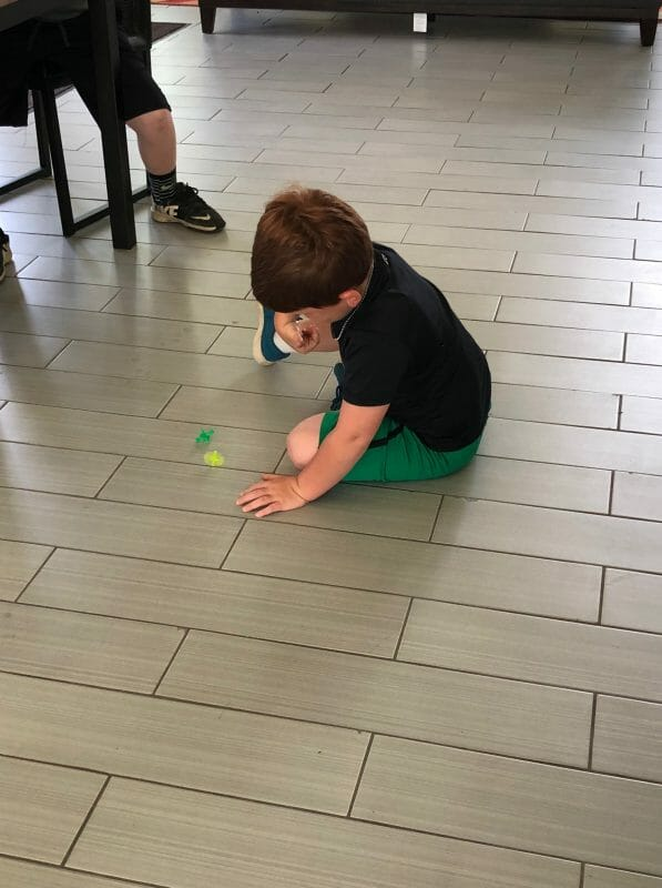 Little boy sitting on floor spinning a top
