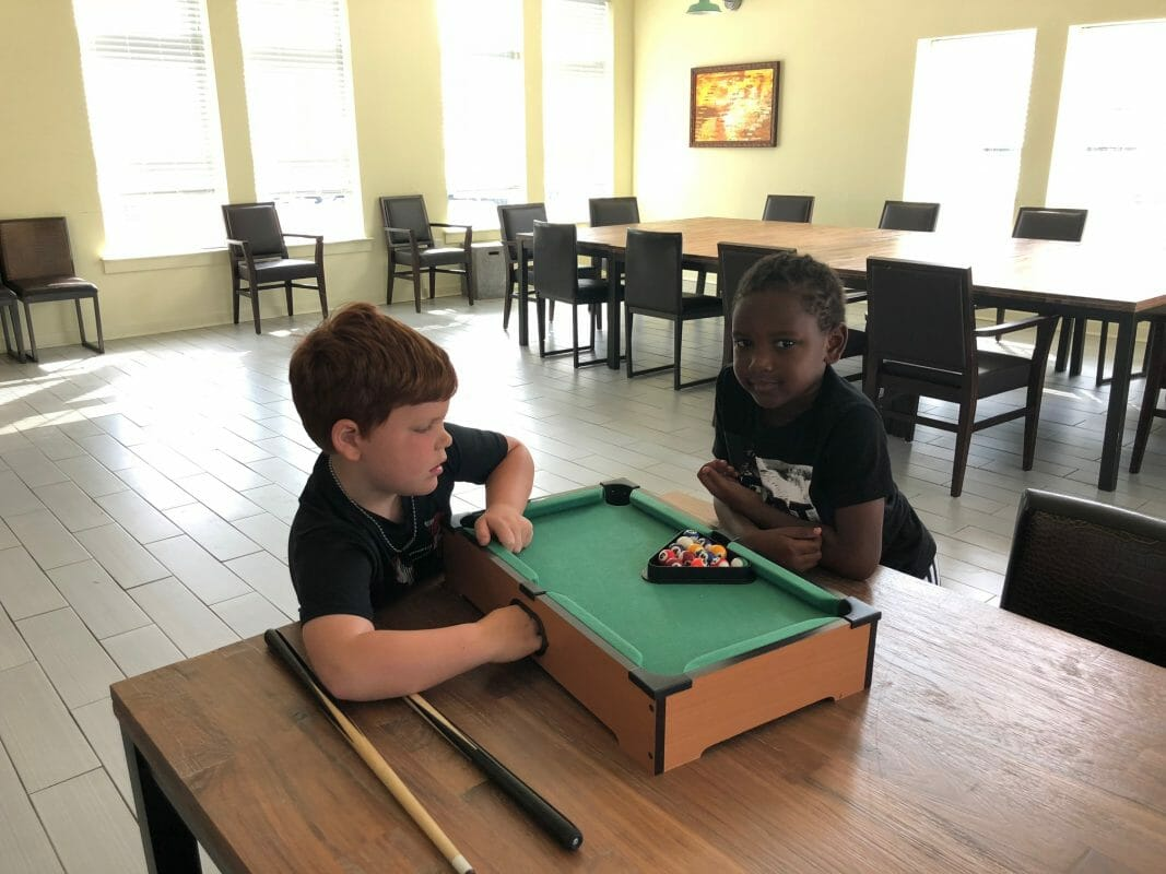 Two kids playing with miniature pool table