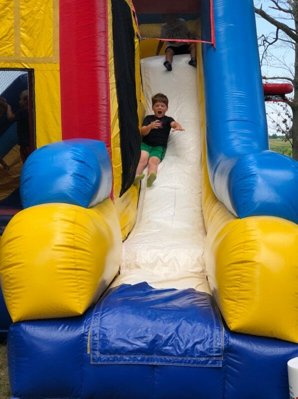 Boy sliding down blow up slide