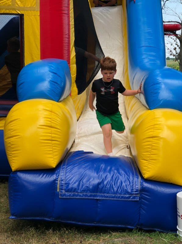 Boy jumping on blow up slide