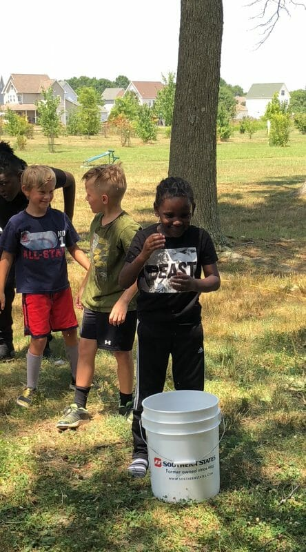 Boys standing around bucket of water