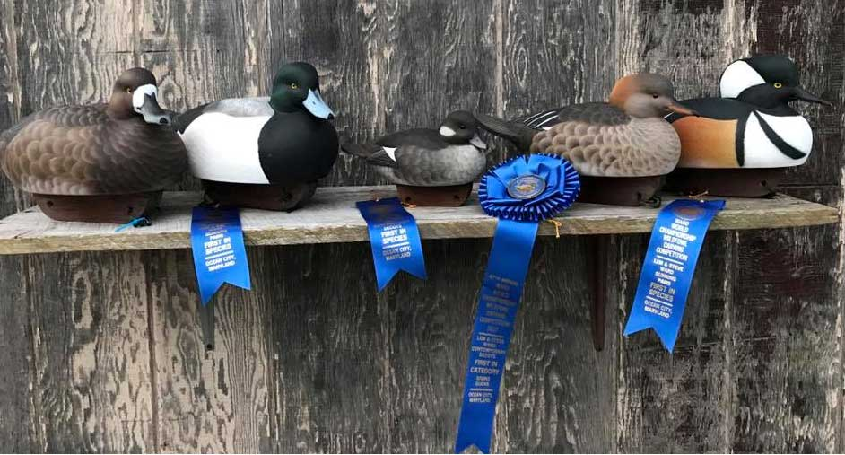 Carved wood ducks with blue ribbons
