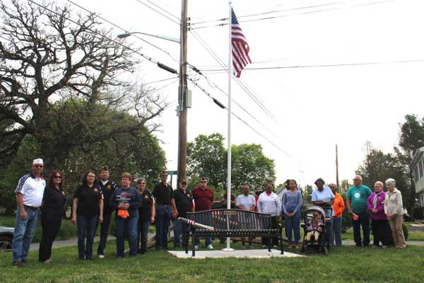 People standing around a flagpole and bench