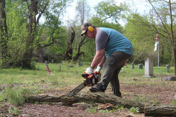 A man uses a chain saw to cut a branch into pieces
