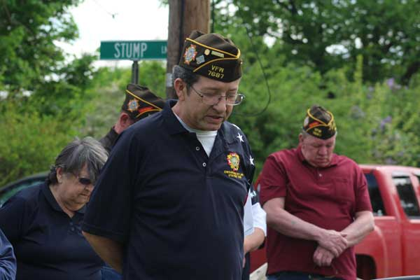 VFW chaplain says prayer with his head bowed