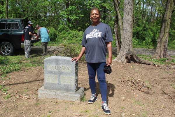 Woman standing with her hand on a gravestone that says Coursey