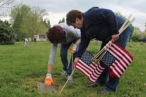 Cecilton town employees Teresa Quinn and Kim Roland place a flag next to the grave of a military veteran