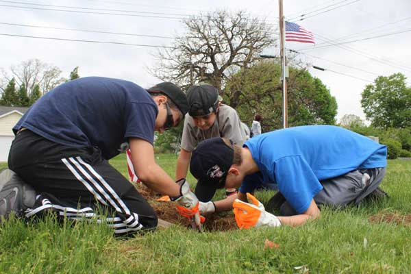 Three boys clearing dirt off of a grave with American flag in background