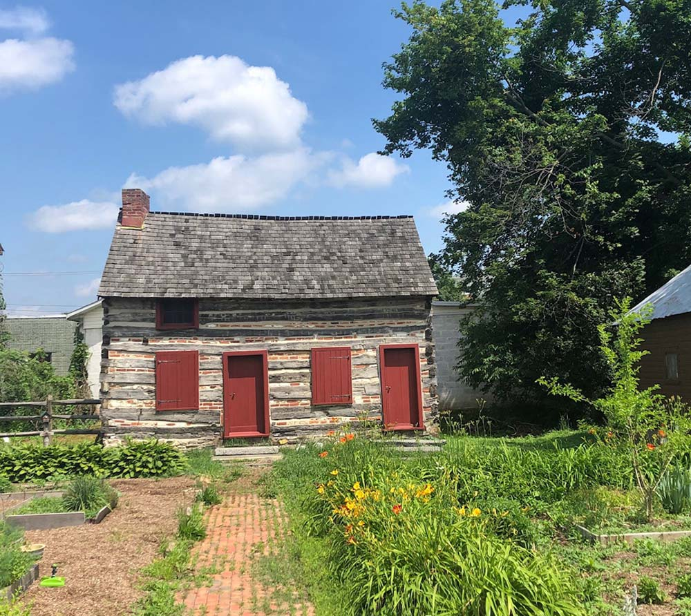 Duke Log cabin with garden in front and a blue sky